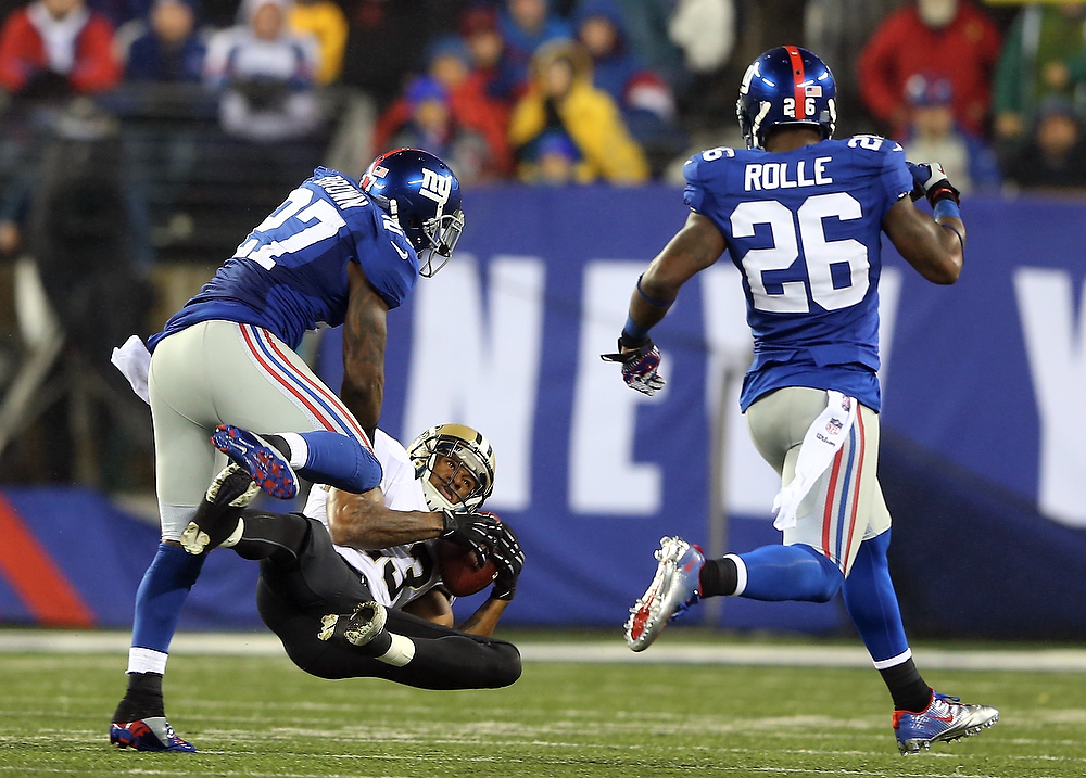 Description of . Joe Morgan #13 of the New Orleans Saints makes the catch as  Stevie Brown #27 and  Antrel Rolle #26 of the New York Giants defend on December 9, 2012 at MetLife Stadium in East Rutherford, New Jersey.  (Photo by Elsa/Getty Images)