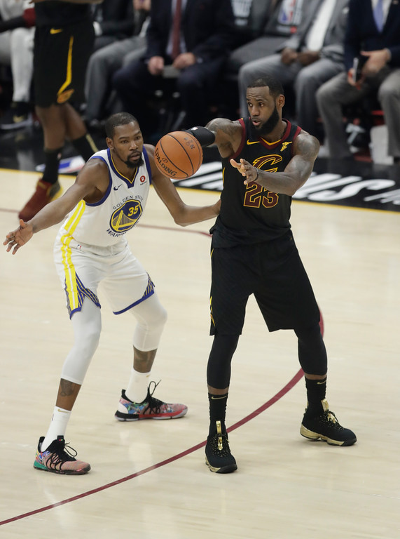 . Cleveland Cavaliers\' LeBron James makes a pass against Golden State Warriors\' Kevin Durant in the first half of Game 4 of basketball\'s NBA Finals, Friday, June 8, 2018, in Cleveland. (AP Photo/Tony Dejak)