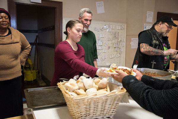04/06/18 Wesley Bunnell | Staff Morelle Warner, L, watches as fellow volunteer Andrianna Baez serves a plate of food during a feed the hungry dinner on Friday evening. St. Mark's Church Sexton Kelly Nauss looks on, middle, as volunteer Bernie Boucher, R, starts to prepare another plate. Warner, known affectionately as Momma, prepares most of the meals the church serves every Friday from 5-6pm for approximately 70-100 individuals relying in large part to donations from the community.