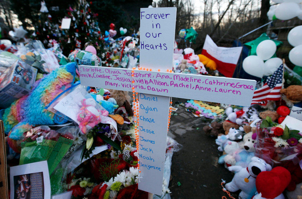 Description of . A cross bearing all the names of the victims of the shootings at Sandy Hook Elementary School in Newtown Connecticut December 14, stands at a makeshift memorial for victims of the shootings in Sandy Hook village in Newtown, December 19, 2012. Six victims of the Newtown school shootings will be honored at funerals and remembrances on Wednesday.  REUTERS/Mike Segar