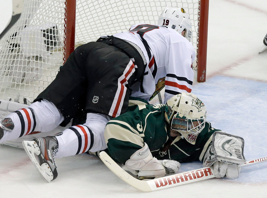 . Chicago\'s Jonathan Toews, left, falls on Wild goalie Josh Harding as Harding stoped a shot by Toews in the first period. Harding was injured on the play and left the game after the first period. (AP Photo/Jim Mone)