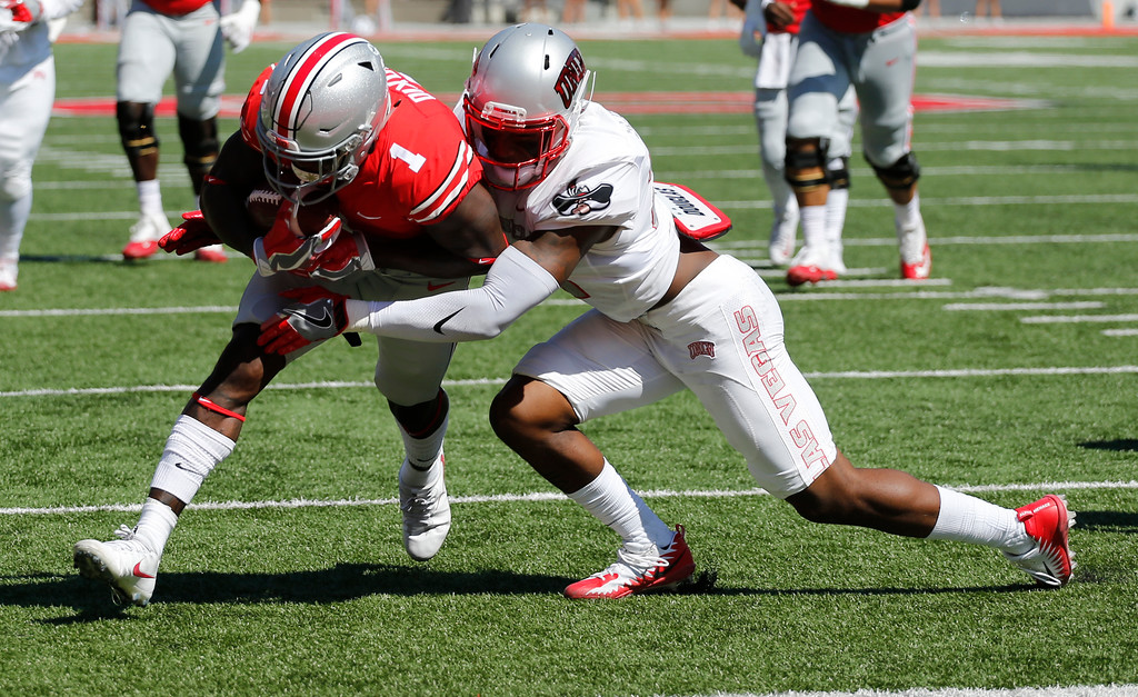 . Ohio State receiver Johnnie Dixon, left, crosses the goal line as UNLV defensive back Chauncey Scissum tries to make the tackle during the first half of an NCAA college football game Saturday, Sept. 23, 2017, in Columbus, Ohio. (AP Photo/Jay LaPrete)