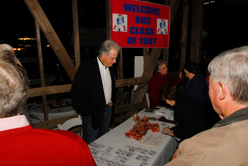 "Greg Wolfrey, standing, works the ""check-in"" table at The Barn."