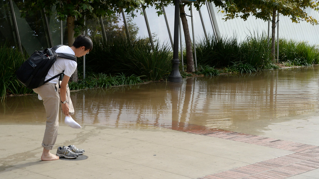 . July 29,2014. Westwood CA,  UCLA students make their way through deep water after a major water main break sent a geyser of water blasting through Sunset Boulevard north of the UCLA campus Tuesday, sending mud and water cascading down the street and inundating a number of vehicles as it made its way onto the campus. Photo by Gene Blevins/LA DailyNews
