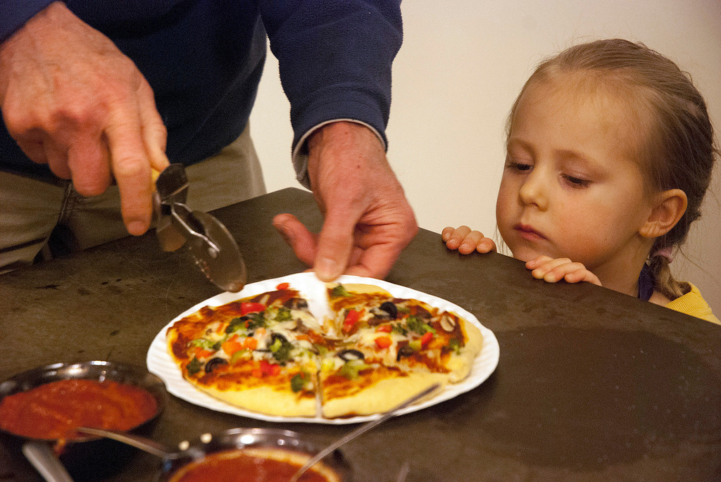 . Kayla Rice/Reformer Lupin Norrichs, 3, of Brattleboro looks on as her pizza is cut. Norrichs participated in the pizza cooking class as part of the Winter Carnival at the Brattleboro Food Co-Op on Friday afternoon.