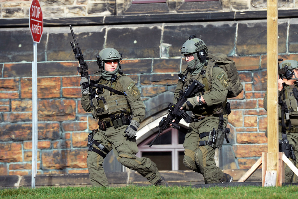 . A Royal Canadian Mounted Police intervention team responds to a reported shooting at Parliament building in Ottawa, Wednesday, Oct. 22, 2014. A soldier standing guard at the National War Memorial has been shot by an unknown gunman and there have been reports of gunfire inside the halls of Parliament. (AP Photo/The Canadian Press, Adrian Wyld)