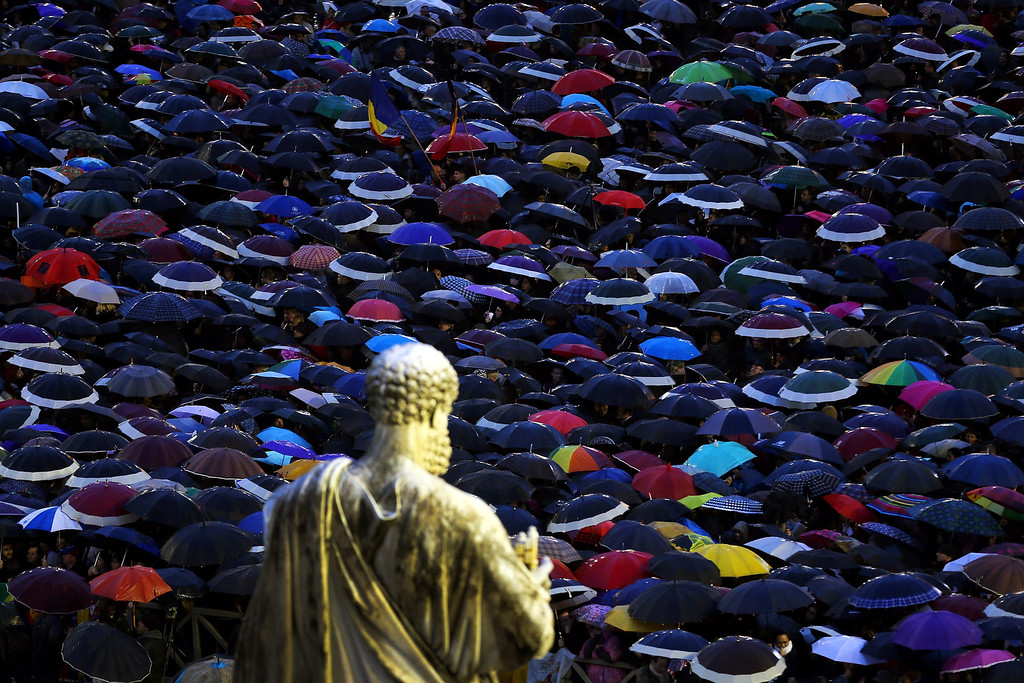 . A statue of St Peter looks down upon people sheltering from the rain under umbrellas as they gather in St Peter\'s Square as they wait for news on the election of a new Pope on March 13, 2013 in Vatican City, Vatican.  (Photo by Joe Raedle/Getty Images)