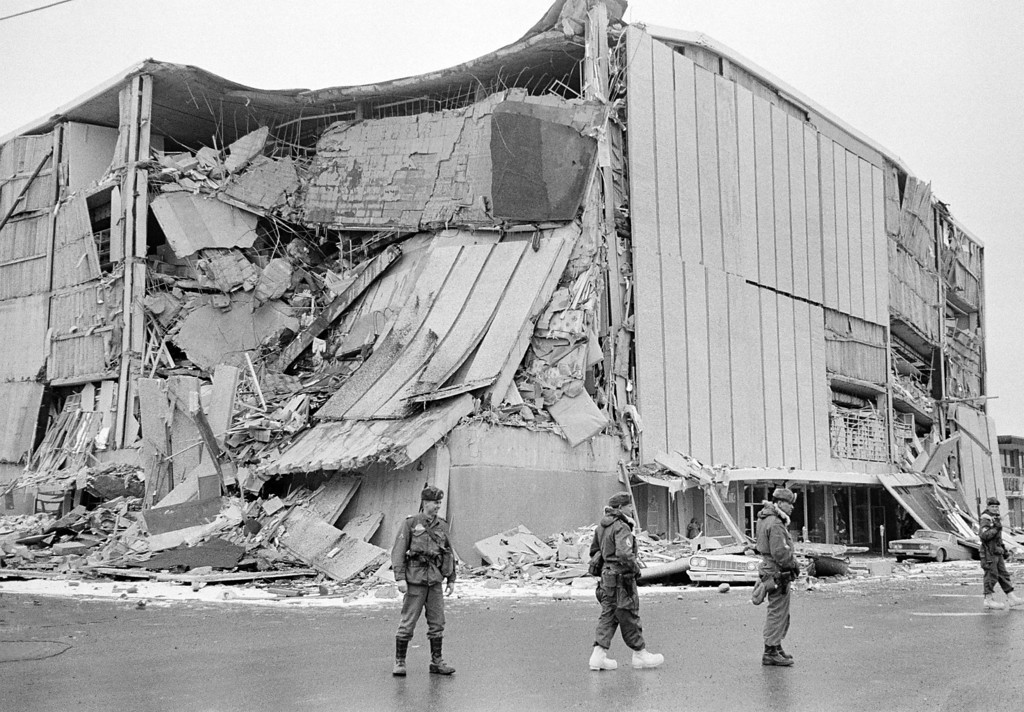 . In this March 28, 1964 file photo, with the city under martial law, soldiers patrol a downtown street in Anchorage, Alaska. In background is the wreckage of the five-story Penney store at Fifth Avenue and D Street. (AP Photo/File)