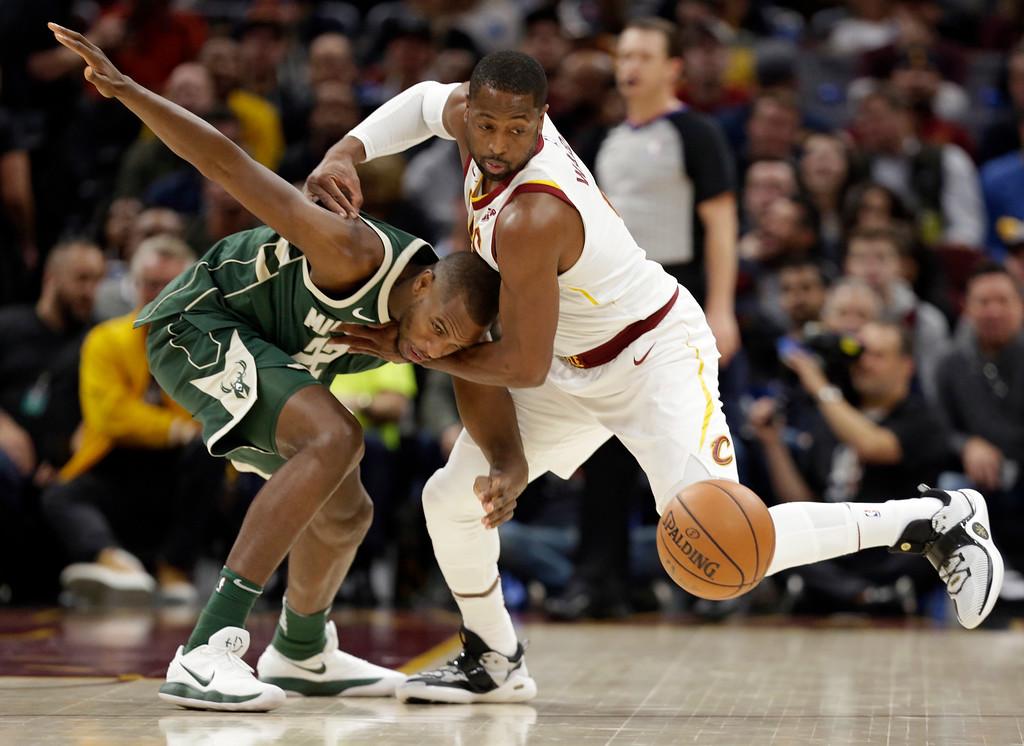 . Milwaukee Bucks\' Khris Middleton, left, and Cleveland Cavaliers\' Dwyane Wade battle for a loose ball in the first half of an NBA basketball game, Tuesday, Nov. 7, 2017, in Cleveland. (AP Photo/Tony Dejak)
