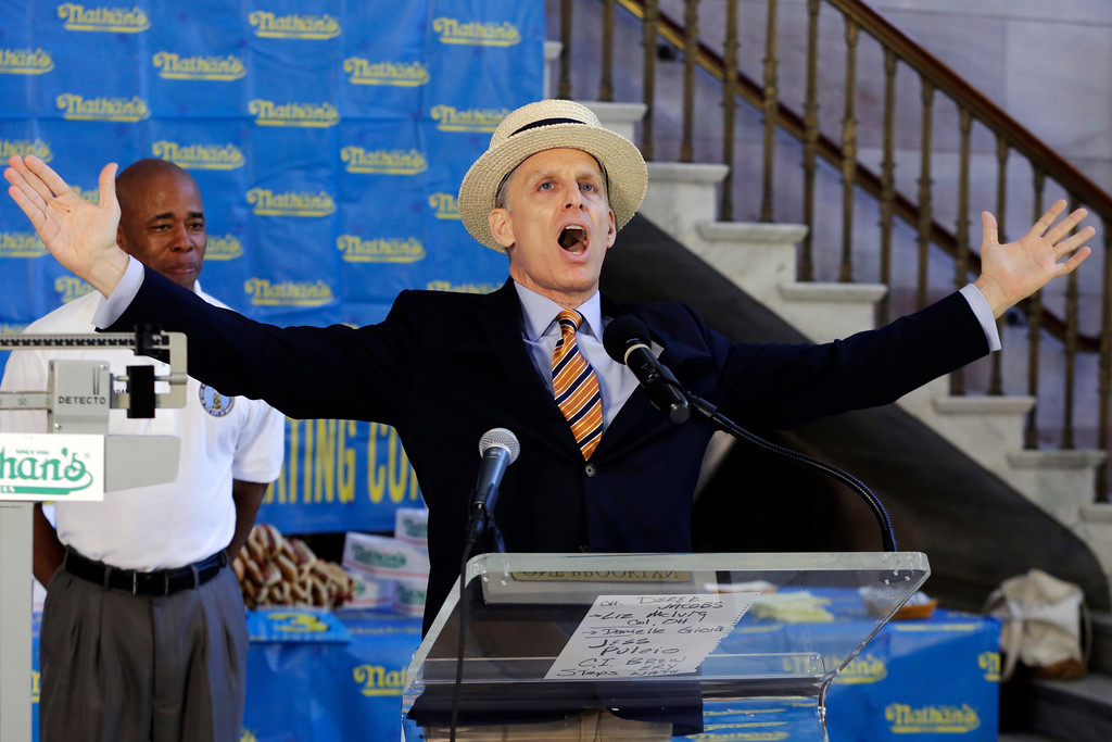 . George Shea, master of ceremonies for the Nathan\'s Hot Dog Eating Contest, gives a sample of his introductions for the event, during the weigh-in for the 2017 contest , in Brooklyn Borough Hall, in New York, Monday, July 3, 2017. At left is Brooklyn Borough President Eric Adams. (AP Photo/Richard Drew)