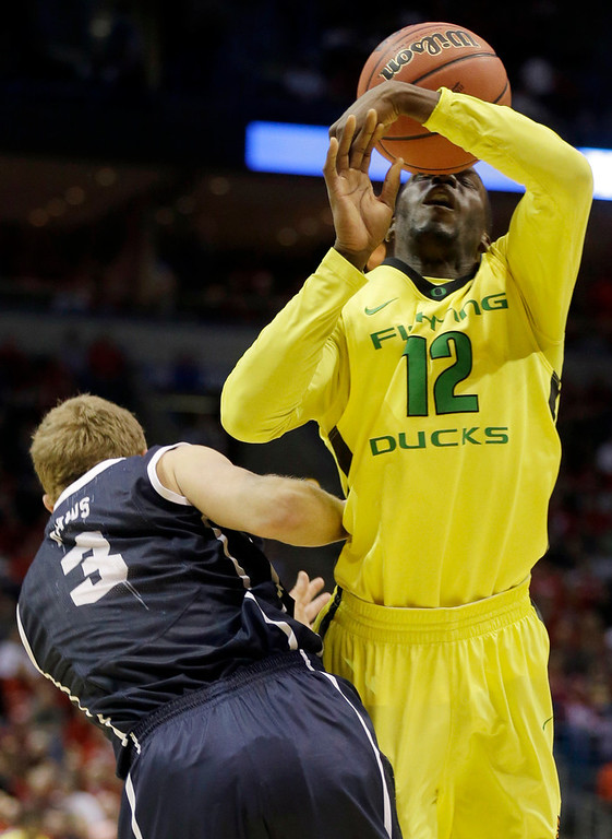 . Oregon guard Jason Calliste (12) is fouled by BYU guard Tyler Haws (3) during the first half of a second-round game in the NCAA college basketball tournament Thursday, March 20, 2014, in Milwaukee. (AP Photo/Jeffrey Phelps)