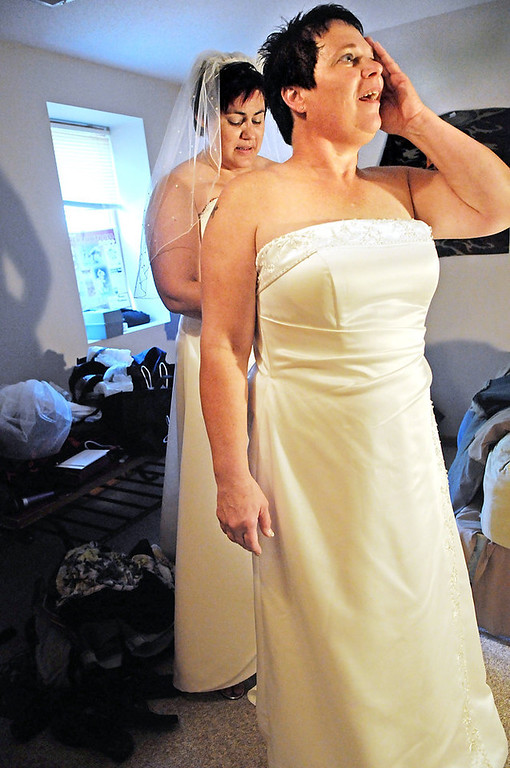 ". ""I hope she hurries up \'cuz I\'m sweating,\"" said Shirley Otto, right, who wipes sweat from her face as Rochelle \""Shay\"" Imdieke ties the back of her wedding dress in a friend\'s house in South St. Paul before their marriage ceremony at Como Park. \""I\'m the tortoise and you\'re the hare,\"" said Imdieke.  (Pioneer Press: Jean Pieri)"