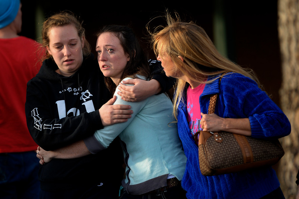 . CENTENNIAL, CO. - December 13: (center) Jenni Meyers 17 year old senior is comforted by her older sister Mary Myers (left) and mom Julie as they leave Shepherd of the Hills church during a lockdown when a student carried a shotgun into Arapahoe High School and opened fire on Friday, wounding two fellow students before apparently killing himself December 13, 2013 Centennial, CO. (Photo By Joe Amon/The Denver Post)