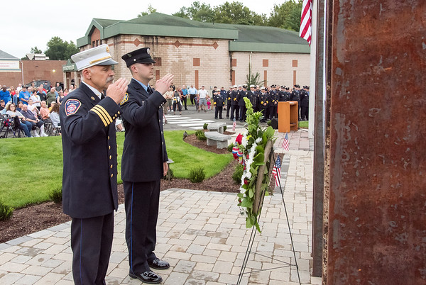 09/11/18 Wesley Bunnell | Staff Berlin officially dedicated its 9/11 Memorial in front of the Kensington Fire Department on Tuesday afternoon featuring steel beams from the World Trade Center. Friend of Berlin Fire Department New Britain Deputy Chief Paul Walsh, L, salutes along with his son Kensington Firefighter Tyler Walsh after laying a wreath at the monument.