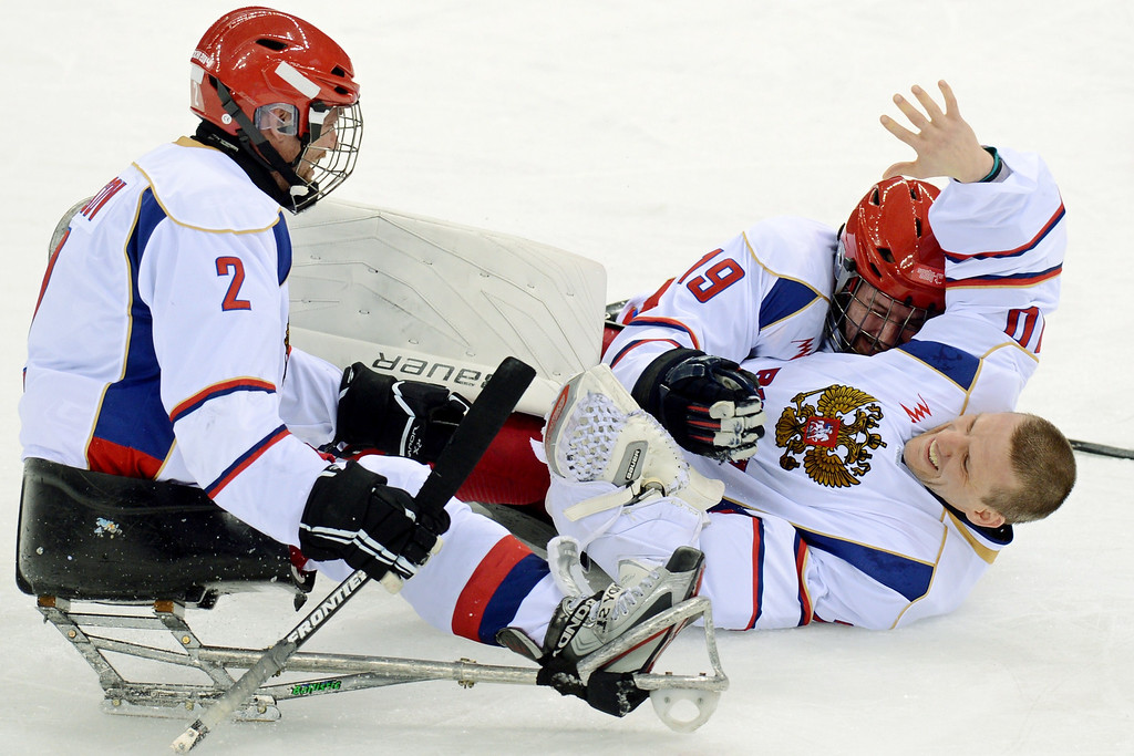 . Russia\'s goalie Vladimir Kamantcev (R) celebrates with teammates after winning their ice sledge hockey match against the USA during the XI Paralympic Olympic games at the Shayba stadium, near Sochi on March 11, 2014. AFP PHOTO / KIRILL KUDRYAVTSEV