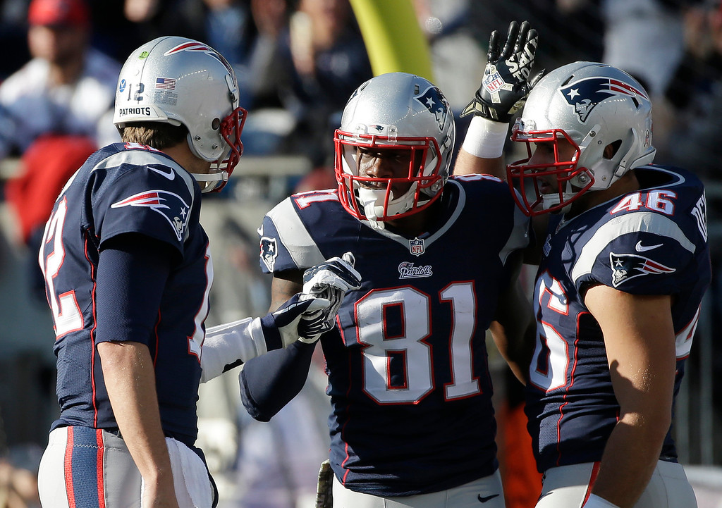 . New England Patriots quarterback Tom Brady, left, celebrates his touchdown pass to New England Patriots tight end Timothy Wright (81) in the first half of an NFL football game against the Detroit Lions Sunday, Nov. 23, 2014, in Foxborough, Mass. (AP Photo/Steven Senne)