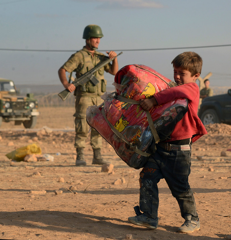 . Turkish soldiers stand guard as a Syrian refugee boy carries his belongings at the border in Suruc, Turkey, late Saturday, Sept. 20, 2014. (AP Photo)