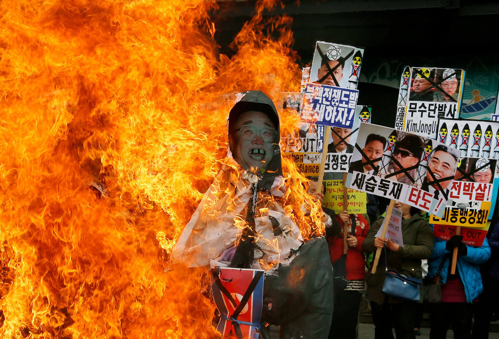 ". South Korean protesters burn effigies of North Korean leader Kim Jong-Un, and late leaders Kim Jong Il and Kim Il Sung at an anti-North Korea protest on the birthday of Kim Il Sung in Seoul, South Korea Monday, April 15, 2013. South Korea\'s defense minister, Kim Kwan-jin, told a parliamentary committee in Seoul on Monday that North Korea remains ready to launch a missile from its east coast, though he declined to disclose how he got the information. The sign at center showing images of the Kim family reads ""Throw Them Out.\""  (AP Photo/Kin Cheung)"
