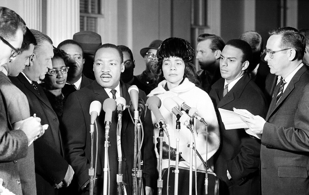 . Dr. Martin Luther King Jr., this year\'s Nobel Peace Prize winner, talks to reporters at the White House, in Washington, D.C., on December 18, 1964, following a conference with U.S. President Johnson. King quoted the president as saying Johnson was determined to end discrimination in voting privileges.  (AP Photo)