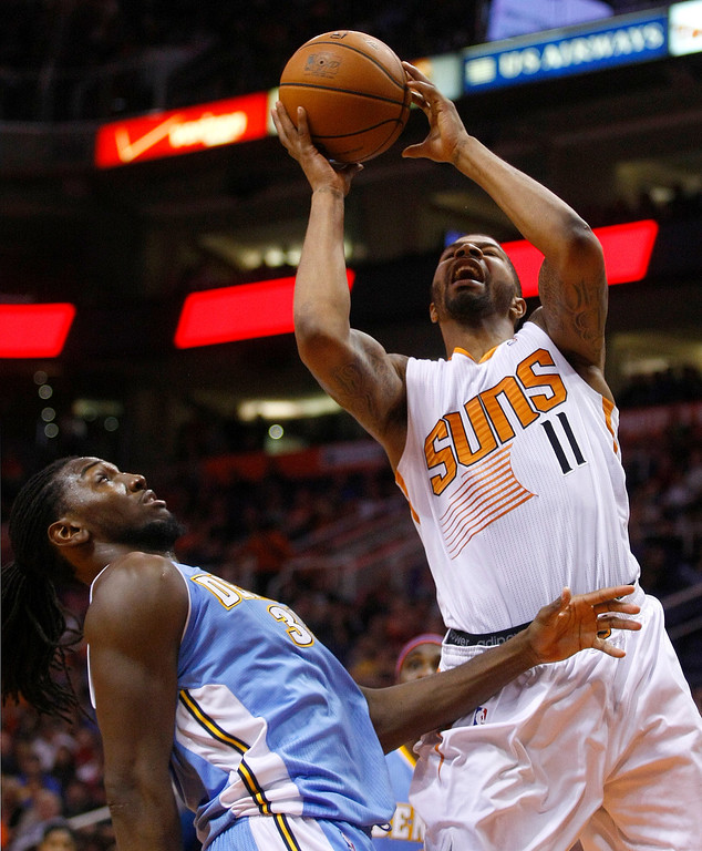 . Phoenix Suns power forward Markieff Morris (11), right, draws the foul and scores on Denver Nuggets power forward Kenneth Faried (35) in the fourth quarter during an NBA basketball game on Friday, Nov. 8, 2013, in Phoenix. The Suns defeated the Nuggets 114-93. (AP Photo/Rick Scuteri)
