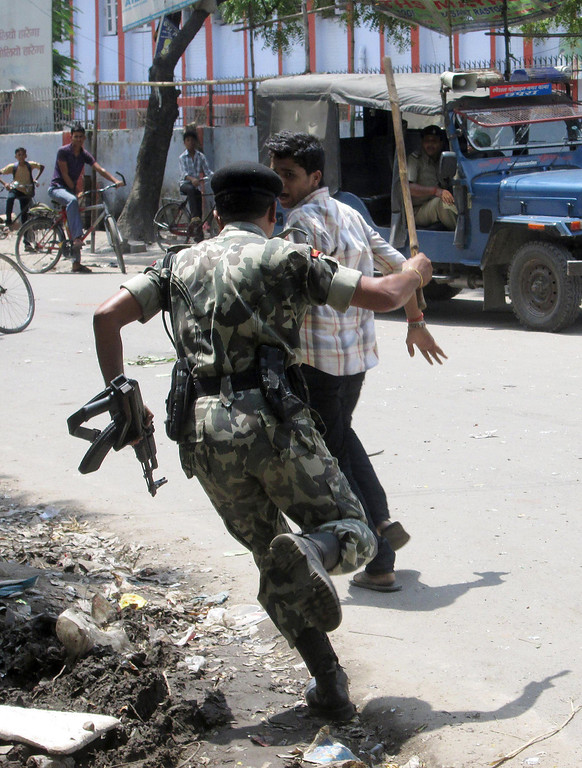 . An Indian policeman beats a youth protesting the deaths of schoolchildren who consumed a free mid day meal at a school in the Saran district of Bihar state, in Chhapra on July 17, 2013.  Twenty-two children have died after eating a free lunch feared to contain poisonous chemicals at an Indian primary school, officials said, as the tragedy sparked angry street protests.  AFP PHOTOSTR/AFP/Getty Images