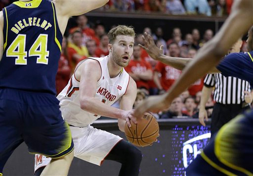 . Maryland forward Evan Smotrycz looks for a teammate as he is pressured by Michigan players in the second half of an NCAA college basketball game, Saturday, Feb. 28, 2015, in College Park, Md. (AP Photo/Patrick Semansky)