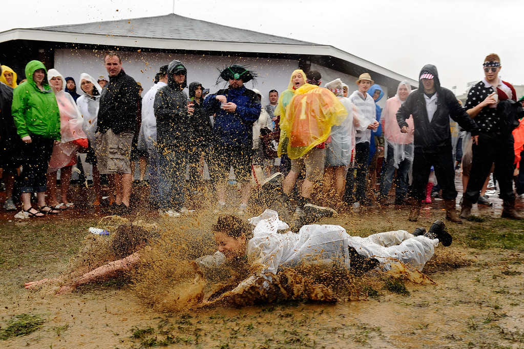 . LOUISVILLE, KY - MAY 04:  Fans slide through the mud in the infield prior to the 139th running of the Kentucky Derby at Churchill Downs on May 4, 2013 in Louisville, Kentucky.  (Photo by Getty Images/Getty Images)