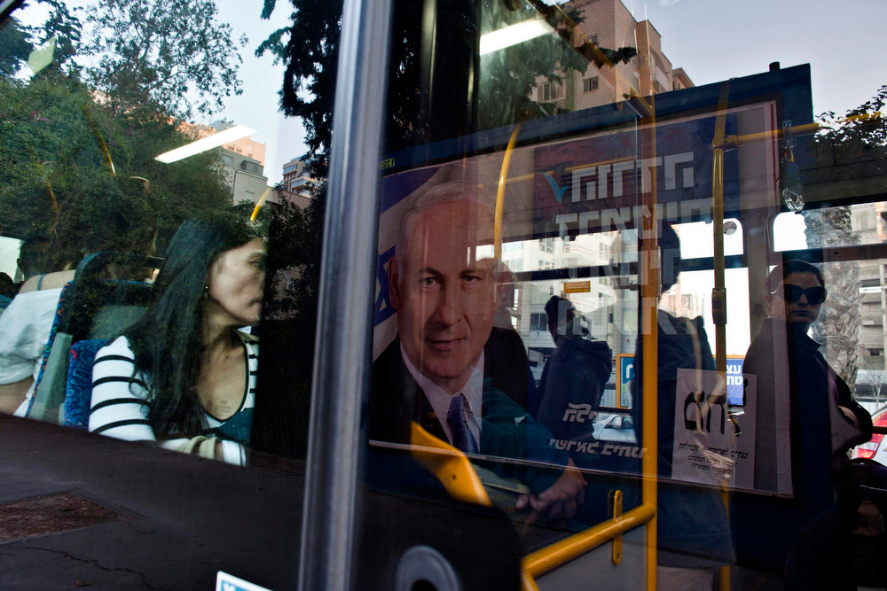 Description of . A banner depicting Israel's Prime Minister Benjamin Netanyahu is reflected on a bus window in Tel Aviv January 21, 2013. Netanyahu made an election-eve appeal on Monday to wavering supporters to