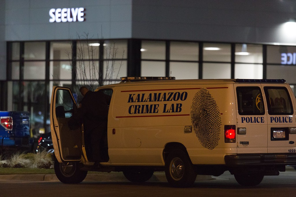 . An officer with the Kalamazoo Crime Lab leaves the scene of a random shooting on Sunday, Feb. 21, 2016 in Kalamazoo. Jason Dalton of Kalamazoo County was arrested early Sunday in downtown Kalamazoo following a massive manhunt after several victims were shot at random.  (Bryan Bennett/Kalamazoo Gazette-MLive Media Group via AP) LOCAL TELEVISION OUT; LOCAL RADIO OUT; MANDATORY CREDIT