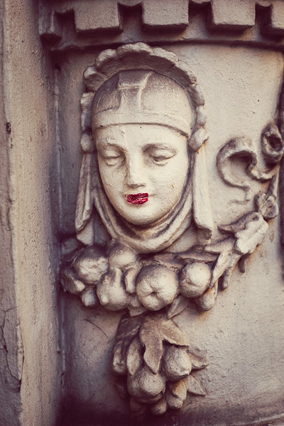 A vandal has put lipstick on a building ornament of a woman.