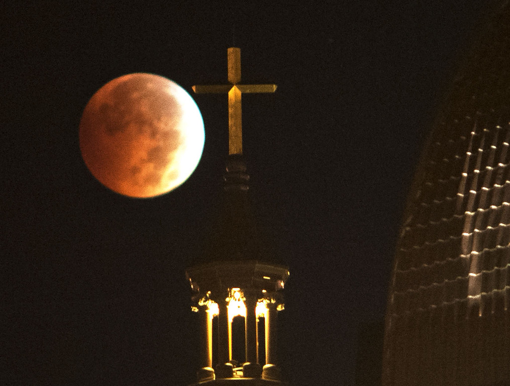. A lunar eclipse appears above the Basilica of St. Adalbert in Grand Rapids, Mich. early Wednesday morning, Oct. 8, 2014.  The moon appears orange or red as it reflects the suns color in the Earth\'s atmosphere. This is known as the blood moon. (AP Photo/The Grand Rapids Press, Chris Clark)