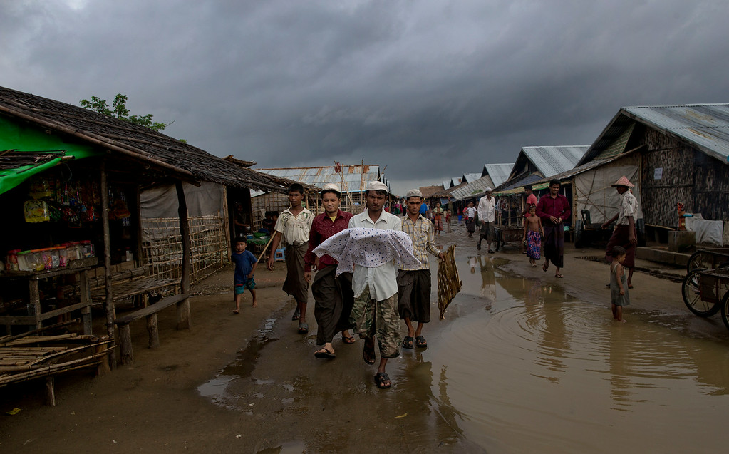 . In this June 27, 2014 photo, 31-year old Yusuf carries the corpse of his niece through a flooded street of a squalid camp for Rohingya refugees in north of Sittwe, Rakhine state, Myanmar. Around 140,000 people have been displaced by sectarian violence in Myanmar\'s western state of Rakhine in the last three years, most of them members of the long-persecuted Muslim minority hunted down by knife-wielding Buddhist mobs. Residents in the camp come out of their bamboo shacks to watch the lonely procession to the burial ground. (AP Photo/Gemunu Amarasinghe)
