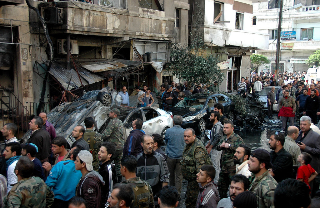 . Syrians gather at the scene of a car bomb explosion in al-Khudary Street, in the Karm al-Loz neighbourhood of the central Syrian city of Homs, on April 9, 2014. More than 150,000 people have been killed in Syria since the conflict began in March 2011, a monitoring group said in a new toll released.  (AFP/Getty Images)
