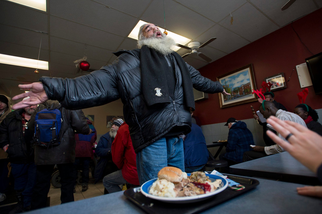 . Moses Gibson dances to choir songs after receiving his Christmas day lunch at the Shepherds of Good Hope in Ottawa, Ontario on Wednesday, Dec. 25, 2013. (AP Photo/The Canadian Press, Justin Tang)