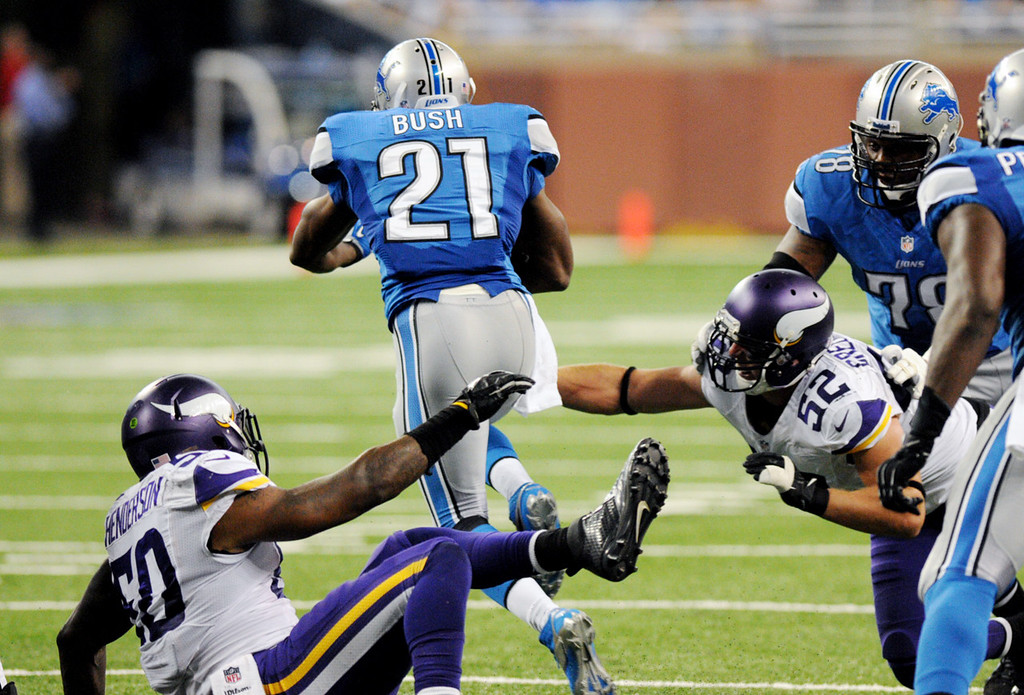 . Lions running back Reggie Bush, center, breaks through the backfield as he eludes Vikings  linebackers Erin Henderson, left, and Chad Greenway in the second quarter.  (Pioneer Press: Chris Polydoroff)