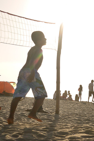 A young boy plays volleyball on the beach at sunset
