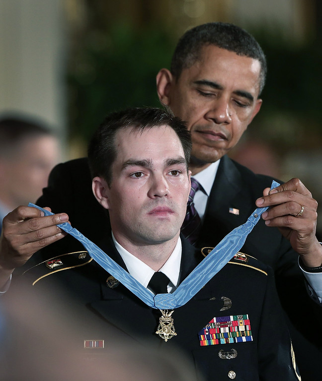 . U.S. President Barack Obama (R) presents the Medal of Honor for conspicuous gallantry to Clinton Romesha (L), a former active duty Army Staff Sergeant, at the White House February 11, 2013 in Washington, DC (Photo by Win McNamee/Getty Images)