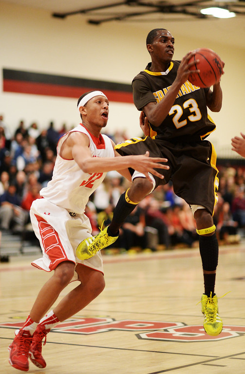 . DENVER, CO. JANUARY 24: Josh McNair of Thomas Jefferson High School (23) controls the ball against Tyre Robinson of East High School (32) during the 1st half of the game at East High School in Denver, Colorado January 24, 2014. East High School won 91-62. (Photo by Hyoung Chang/The Denver Post)