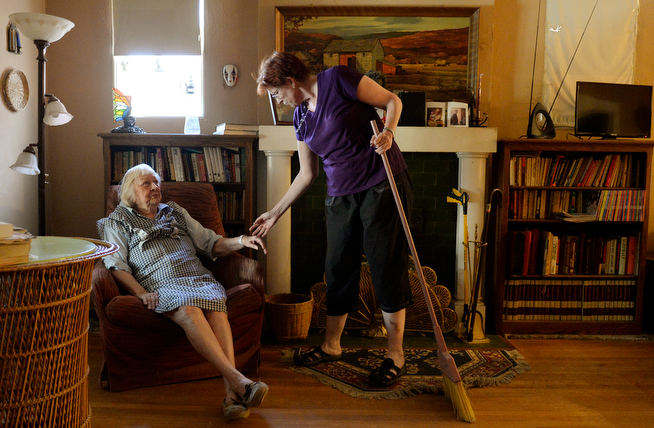 . 92-year-old Mary Brandell gets a weekly visit from Suzanne Liesman of FirstLight Home Care. They chatted in the living room as Liesman swept around Brandell\'s Denver home. Liesman helps Brandell with things around the home on Friday April 11, 2014. (Denver Post Photo by Cyrus McCrimmon)