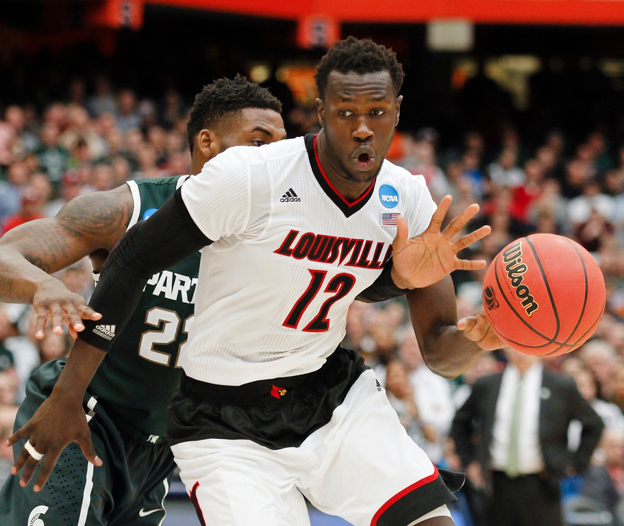 . Louisville\'s Mangok Mathiang (12), of Australia, drives past Michigan State\'s Branden Dawson (22) during the second half of a regional final in the NCAA men\'s college basketball tournament Sunday, March 29, 2015, in Syracuse, N.Y. (AP Photo/Nick Lisi)