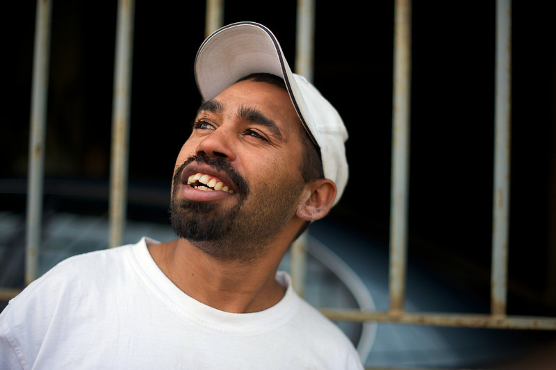 Twenty-six-year-old Aboriginal man in a white t-shirt and hat in front of bars and looking upwards