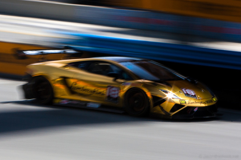 Gold Lamborghini down the front straight at Laguna Seca.