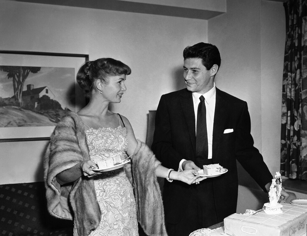 . Actress Debbie Reynolds hands her singing husband Eddie Fisher a piece of cake as they pose at a press conference in Washington, D.C., about 24 hours after their marriage at a Catskill mountain resort, , Sept. 27, 1955,. The couple came to the nation\'s capitol, where they met four years ago, to keep a singing engagement for Eddie. It was the start of a cross-country honeymoon which will include taking in the World Series. Debbie\'s seven-carat, emerald cut diamond engagement ring can easily be seen on her left hand. (AP Photo/Bob Schutz)