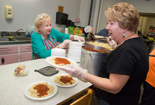 12/05/19 Wesley Bunnell | StaffrrVolunteers at First Lutheran Church in New Britain hold a free pasta dinner every Wednesday night open to all. Barbara Pond, L, Gail Spada, not shown, and Nancy Michalski put togethers the plates of pasta.