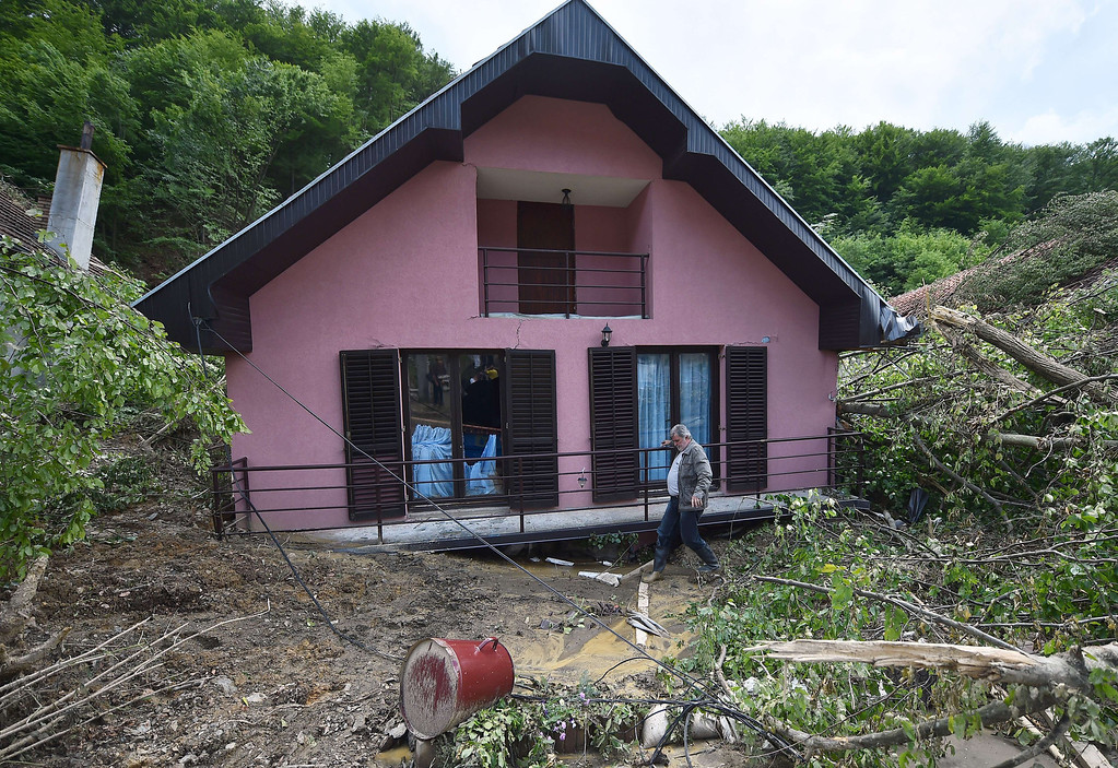 . A man walks past a house damaged by flooding and landslide  in Krupanj, some 130 kilometers south west of Belgrade, on May 20, 2014, after the western Serbian town was hit with floods and landslides, cutting it off for four days. Serbia declared three days of national mourning on May 20 as the death toll from the worst flood to hit the Balkans in living memory rose and health officials warned of a possible epidemic.   AFP PHOTO / ANDREJ  ISAKOVIC/AFP/Getty Images