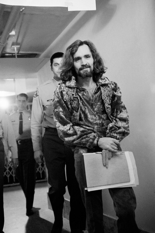 . Charles Manson, leader of the hippie-type cult accused of multiple murders, leaves a Los Angeles courtroom in Los Angeles after approval of his requests for delay of two weeks in his plea and assignment of a private investigator to help him prepare his defense, Jan. 14, 1970 . He is acting as his own attorney. He appeared in a red velvet shirt and vest. (AP Photo/George Brich)