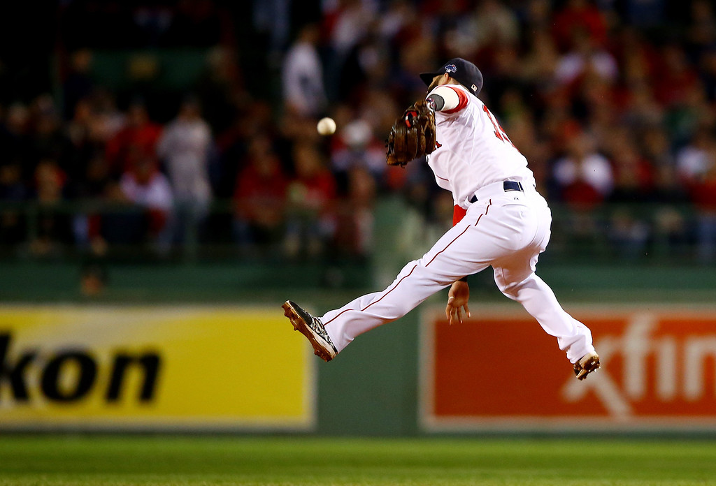 . BOSTON, MA - OCTOBER 12:  Dustin Pedroia #15 of the Boston Red Sox attempts to make a catch against the Detroit Tigers during Game One of the American League Championship Series at Fenway Park on October 12, 2013 in Boston, Massachusetts.  (Photo by Al Bello/Getty Images)