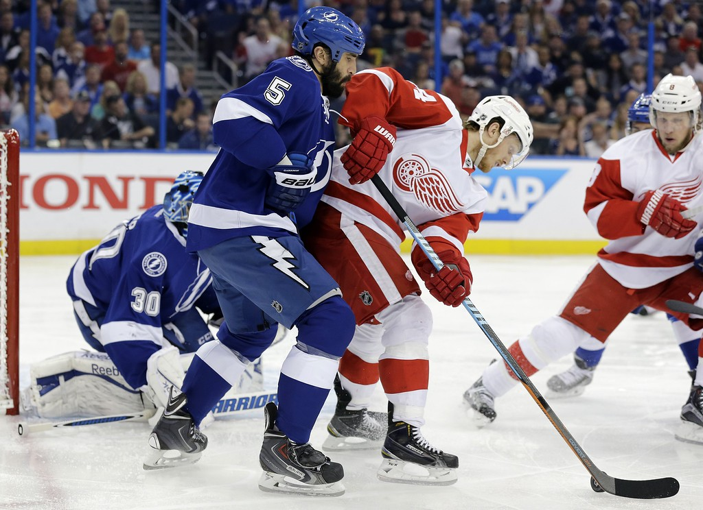 . Detroit Red Wings center Gustav Nyquist, center, tries to back in on Tampa Bay Lightning defenseman Jason Garrison (5) during the first period of Game 7 of a first-round NHL Stanley Cup hockey playoff series Wednesday, April 29, 2015, in Tampa, Fla. (AP Photo/Chris O\'Meara)