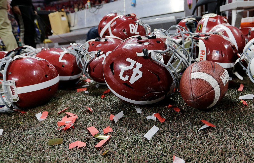 . Alabama helmets lay with confetti after overtime of the NCAA college football playoff championship game against Georgia Monday, Jan. 8, 2018, in Atlanta. Alabama won 26-23. (AP Photo/David J. Phillip)