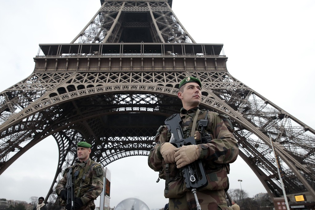 . French soldiers patrol in front of the Eiffel Tower on January 7, 2015 in Paris as the capital was placed under the highest alert status after heavily armed gunmen shouting Islamist slogans stormed French satirical newspaper Charlie Hebdo and shot dead at least 12 people in the deadliest attack in France in four decades. Police launched a massive manhunt for the masked attackers who reportedly hijacked a car and sped off, running over a pedestrian and shooting at officers. AFP PHOTO / JOEL SAGET/AFP/Getty Images